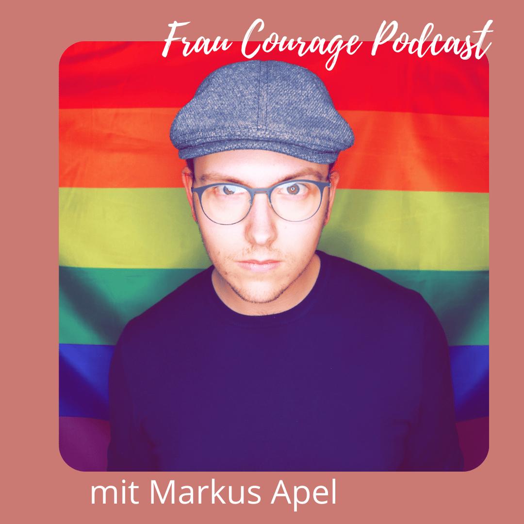 Markus Apel steht vor einer Regenbogenfahne